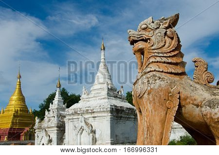 A statue of a lion stands guard over the ruins of Inwa a former capital of Burma located in Mandalay