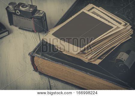 Old photographs and family albums are on the table next to the old camera