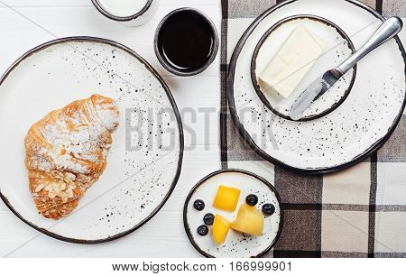 Tasty start of the day. Decent delicious breakfast consisting of croissant, fruits and soft cheese being arranged on bright clean table decorated with checked cloth