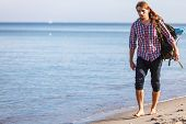 Man hiker backpacker walking with backpack on sea shore at sunny day. Adventure summer tourism active lifestyle. Young long haired guy tramping poster