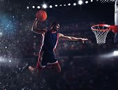 Player throws the ball in the basket in the stadium full of spectators poster