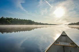 Canoe trip in the morning.  Brilliant and bright mid-summer sunshine morning, paddling a canoe in the middle of quiet, calm and peaceful Corry lake.