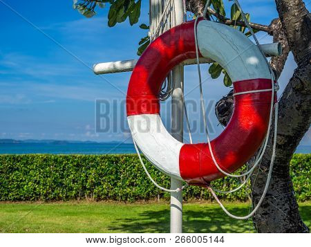 Close Up Lifeguard Ring Or Red White Life Buoy Hanged On The Pole Beside Swimming Pool With Sea And