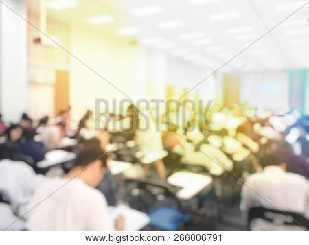 Blurred Image Of Large Examination Room With Students Sitting On Lecture Chair Doing Final Exam, Stu