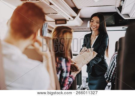 Female Tour Service Employee At Work On Tour Bus. Young Smiling Woman Wearing Black Suit Giving Blan