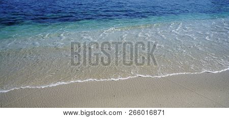 A Background Image Of An Ocean Shoreline Going From Shades Of Dark Blue, Light Blue, To Clear.