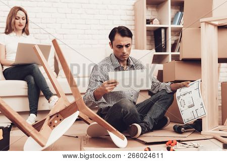 Reading Furniture Instructions. Assemble Furniture. Man Repairing Chair. Man Collects Chair. Furnitu