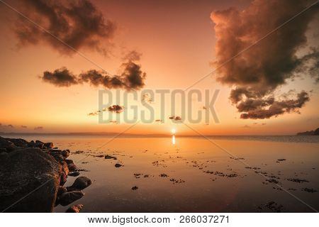 Sunrise Over The Sea By The Shore With Rocks In The Morning Sun