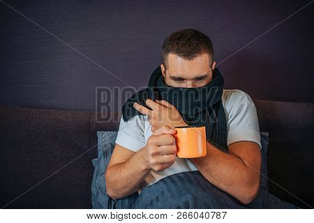 Picture Of Young Sick Man Sitting On Bed And Holding Orange Cup Of Tea. He Looks At It. Guy Coveres