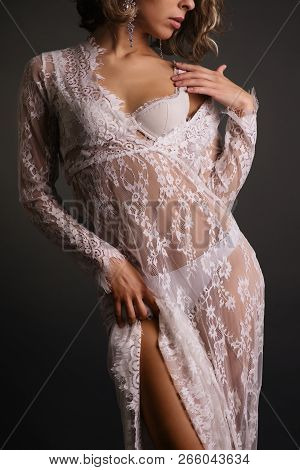Close Up Body Of Young Slim Woman In White Lace Transparent Dress On Dark Background