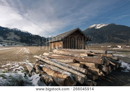 Pile Of Cut Tree Trunks Near A Wooden Cabin, At The Foot Of The Austrian Alps, With Snow Around, Nea