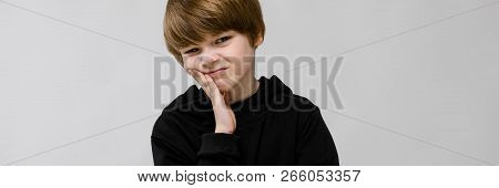 Charming Teenager With Blond Hair And Dark Eyes. The Teenager Propped His Cheek With His Fingers. Th