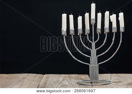 close up view of jewish menorah with candles for hannukah holiday celebration on wooden tabletop isolated on black, hannukah concept poster
