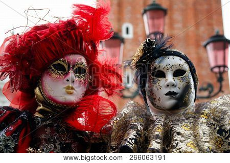 Carnival Pair Red-black-gold Mask And Costume At The Traditional Festival In Venice, Italy