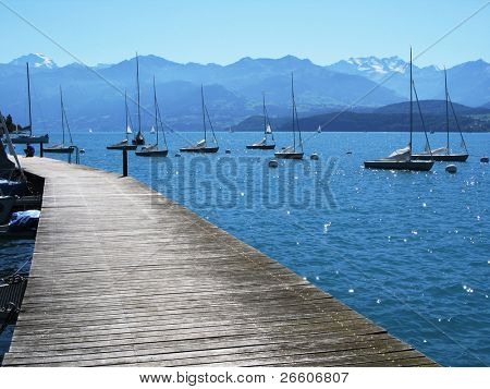 Wooden pier against lake Thun and Alps. Switzerland