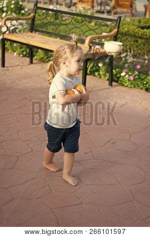 Cute Baby Boy Or Small Little Child With Blond Hair Ponytail In Blue Tshirt And Shorts Walking Baref