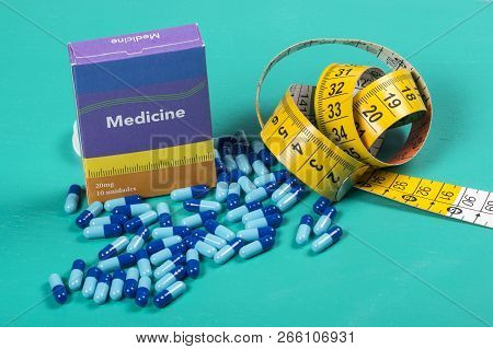Medicine Box With Some Blue Capsule And Measuring Tape In A Green Background.