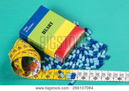 Medicine Box With Some Blue Capsule And Measuring Tape