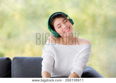 Close Up Shot Portrait Of Young Beautiful Asian Woman Sitting On Sofa  And Listening To Music With H