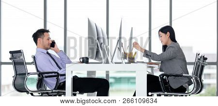 Besinessman And Businesswoman Working Together In Modern Office. Man Is Using Smartphone Calling To
