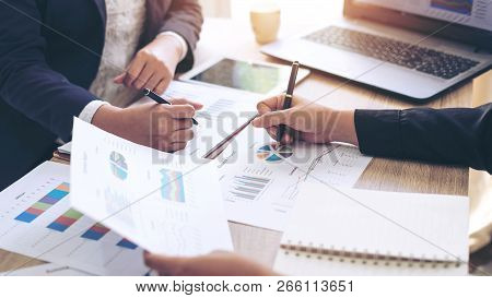 Image Of Two Young Business People Pointing At Business Document During Discussion At Meeting , Note