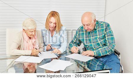 Woman advising senior citizen for finance or home insurance