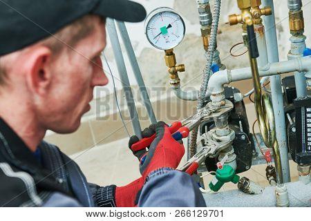 heating engineer or plumber in boiler room installing or adjusting pipeline