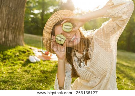 Close up of smilng young girl in summer hat spending time at the park, showing sliced kiwi at her face