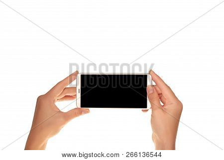Mock-up Of Modern Smartphone In The Hands Of A Girl. Phone In Horizontal Position With A Blank Scree