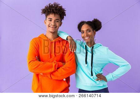 Photo of teen african american couple in colorful clothes smiling while standing together isolated over violet background