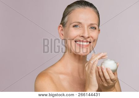 Beautiful mature woman holding jar of moisturizer and looking at camera. Happy senior woman holding a bottle of anti-aging lotion isolated over grey background. Anti aging and beauty treatment.