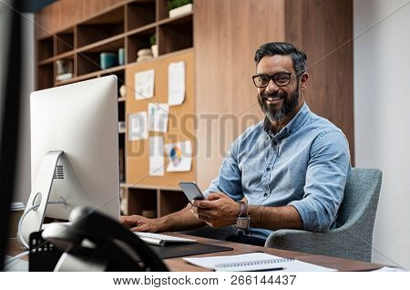 Smiling business man wearing eyeglasses working on desktop computer while using phone in office. Middle eastern businessman using smartphone while sitting at desk in office designer.