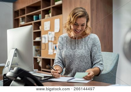 Smiling busy employee in casual reading notes and writing on notebook. Happy mature business woman reading letter and smiling at office. Creative businesswoman taking notes for meeting.