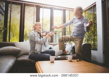 Meaningful Moments. Lover Senior Couple Sing A Song Together. Wife Playing A Violin And Husband Is D