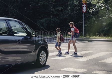 Car In Front Of Children On Pedestrian Crossing Walking From The School And Looking At Their Smartph