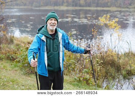 Active Healthy Elderly Bearded Man On Retirement Training Outdoors With Trekking Poles. Attractive S