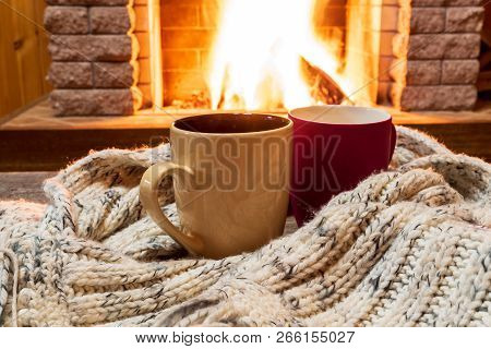 Two Cups For Hot Tea Or Coffee And Cozy Warm Scarf Near Fireplace, In Country House, Winter Vacation