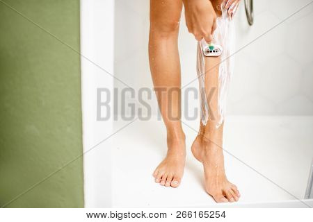 Woman Shaving Her Legs With Razor And Foam In The Shower Cabin