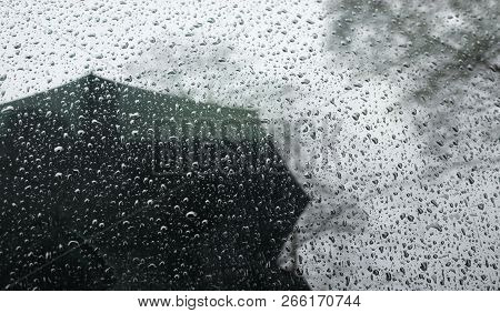 Rainy Weather Reflections In Car Window. Man With An Umbrella Under Rain. Bad Weather