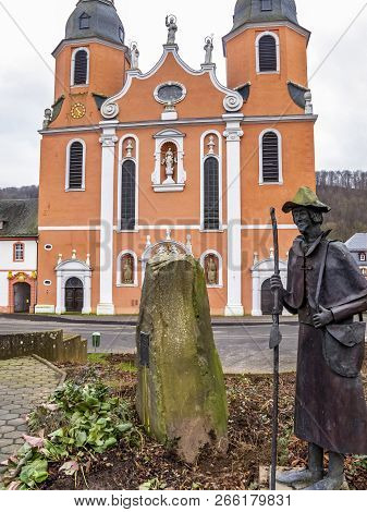 Statue of a pilgrim on the Way of St. James in front of St. Salvator Basilica, the former abbey church of the Pruem Benedictine Abbey at Pruem, Germany poster
