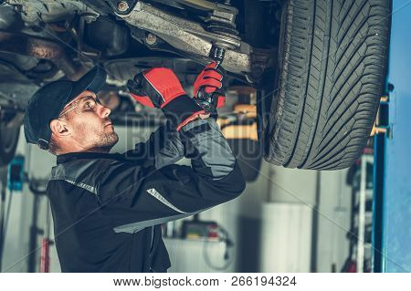 Caucasian Car Mechanic Adjusting Tension In Vehicle Suspension Element. Professional Automotive Serv