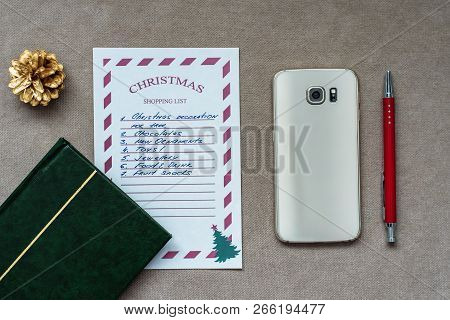Christmas Composition, Christmas Shopping List, Mobile Phone, Pen, Green Note Book, And Golden Fir C