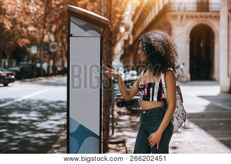 Young Curly Caucasian Female Hipster Is Paying For Parking Using Outdoor Electronic Pay Station Term
