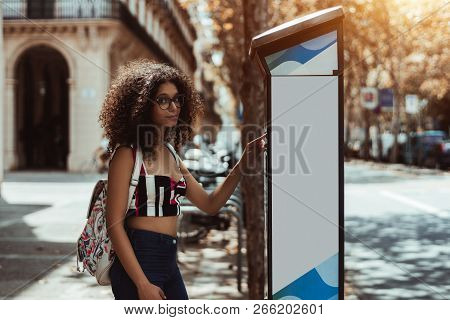 Portrait Of Young Curly Hipster Girl Paying Parking Time Meter Via Electronic Kiosk Outdoors; A Beau