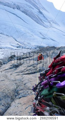 male mountain climber on an exposed climbing route high above a glacier poster