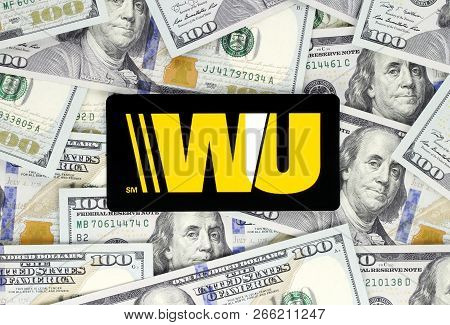 Kiev, Ukraine - September 18, 2018: Western Union Logo Printed On Paper, Cut And Placed On Money Bac
