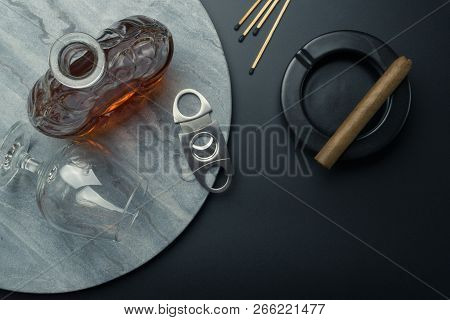 Top View Of A Brandy Decanter And A Snifter Glass With A Stainless Steel Cigar Cutter On The Marble