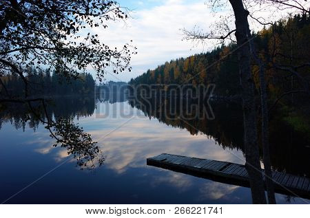 Nature of Sweden in autumn, Calm Stora Kedjen lake with wooden bridge and reflecting forest, Peaceful outdoor image