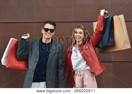 Beautiful Young Loving Couple Carrying Shopping Bags And Enjoying Together. Picture Showing Young Co