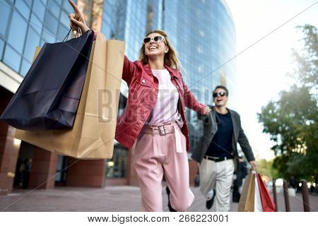 Front View Of A Casual Couple Of Shoppers Running In The Street Towards Camera Holding Colorful Shop
